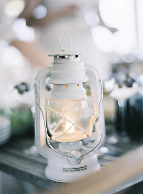 Lit up small white lantern on table — Stock Photo