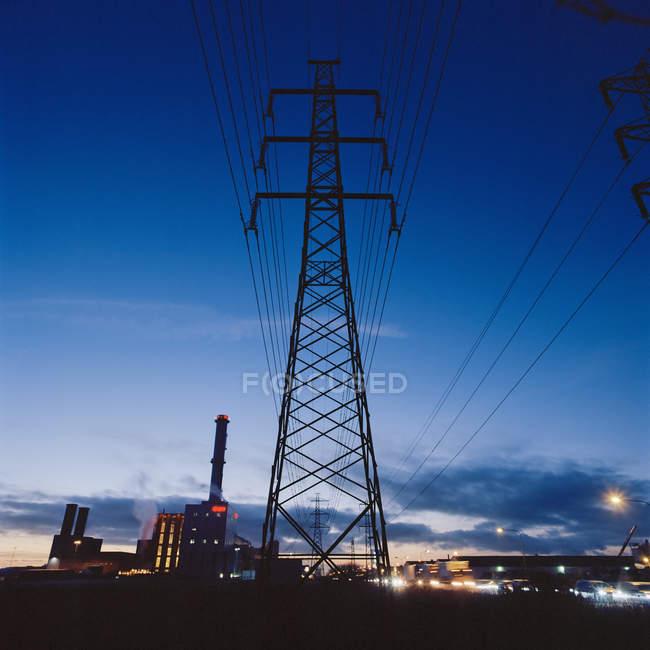 Город освещается в сумерках и электрических столбах — стоковое фото