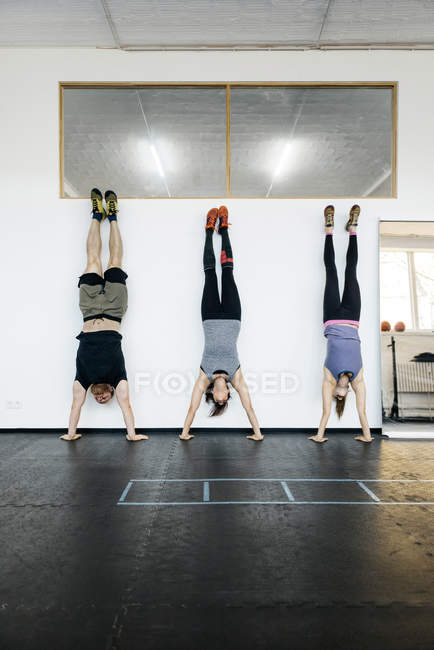 Young women and man practicing handstand in gym — Stock Photo
