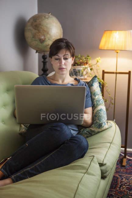 Donna con capelli marroni utilizzando il computer portatile sul sofà — Foto stock