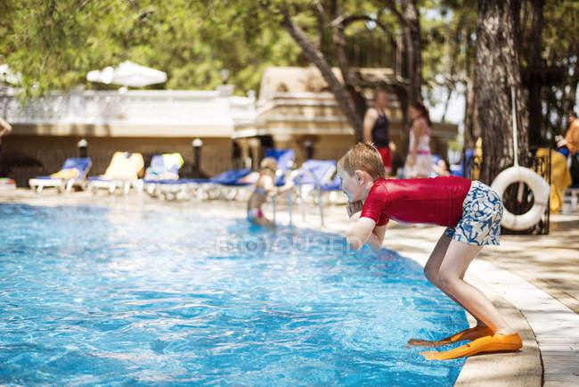 Хлопчик носіння дайвінг тапочки стрибати в басейн готелю holiday resort — стокове фото