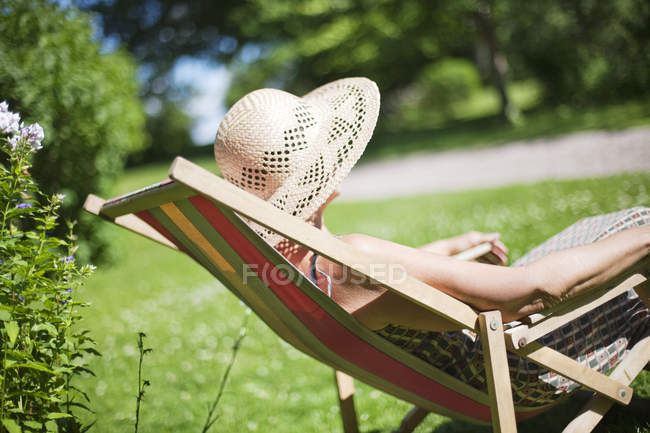 Side view of senior woman relaxing on sun chair — Stock Photo