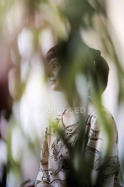 Young woman seen through leaves, selective focus — Stock Photo