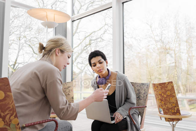 Women looking at smartphone screen while sitting in library — Stock Photo