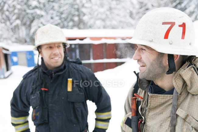 Firefighters in front of station, focus on foreground — Stock Photo