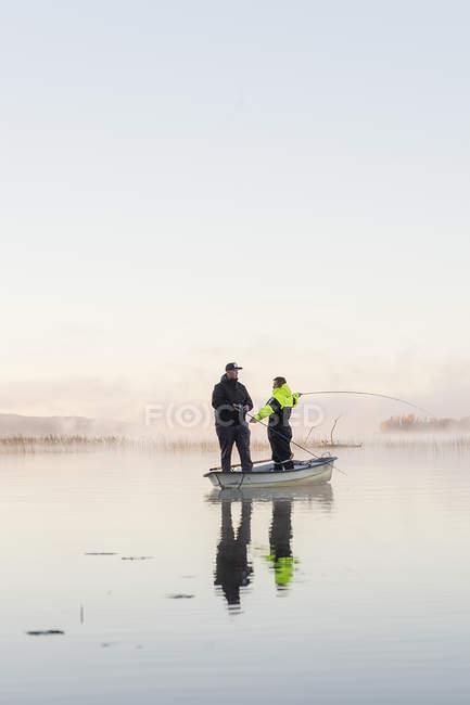 Young men fishing in lake at sunset — Stock Photo