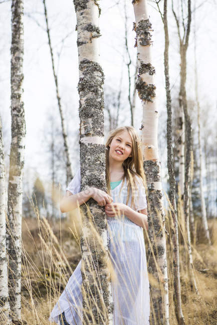 Smiling girl standing by birch tree in forest — Stock Photo