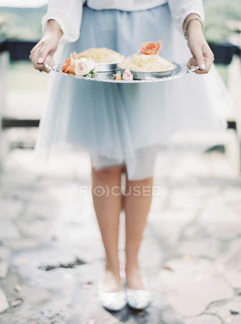 Frau im eleganten Rock mit silbernen Tablett mit Desserts, beschnitten Schuss — Stockfoto