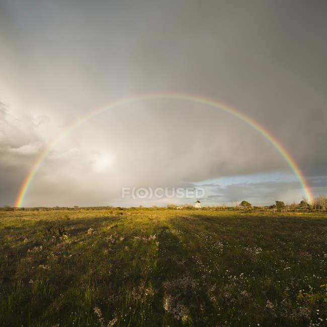Arcobaleno sopra il campo verde in cielo nuvoloso — Foto stock