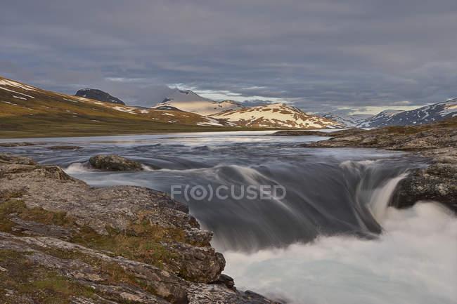 Живописный вид на водопад и горную цепь — стоковое фото