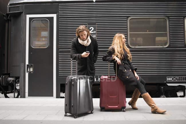 Молоді пара з багажем чекає поїзда — стокове фото