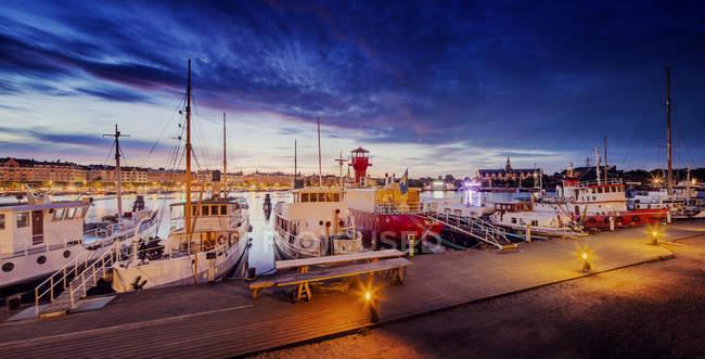 View of harbor with sailboats illuminated at night, Stockholm — Stock Photo