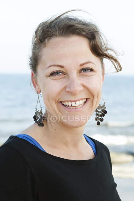 Ritratto di donna che guarda la macchina fotografica, mare sullo sfondo — Foto stock