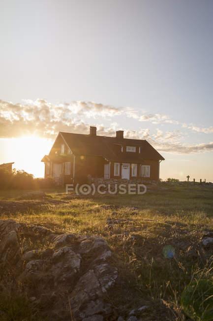Casa de madera en colina verde al atardecer - foto de stock