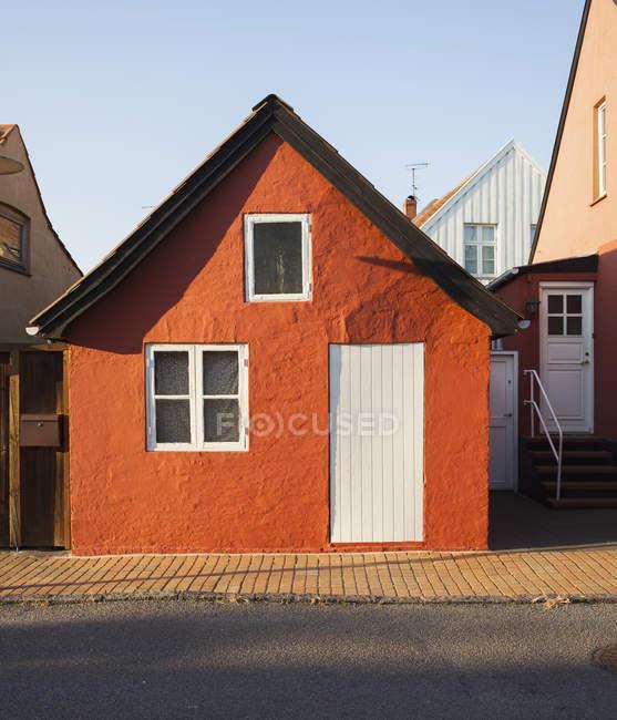 Vista frontal de la casita roja en la luz del sol - foto de stock
