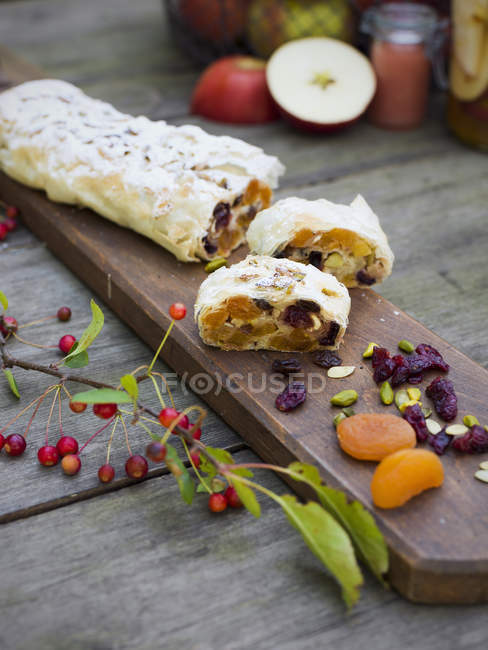 Apple and apricot in filo pastry on cutting board on table — Stock Photo