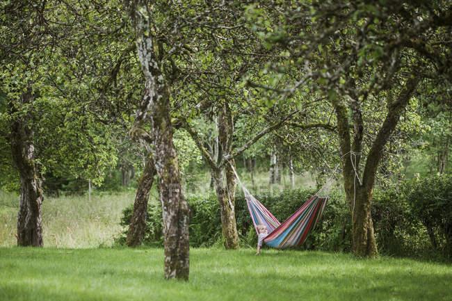 Menina deitada na rede no jardim, foco seletivo — Fotografia de Stock