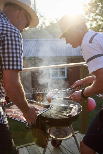 Two men grilling fish, focus on foreground — Stock Photo