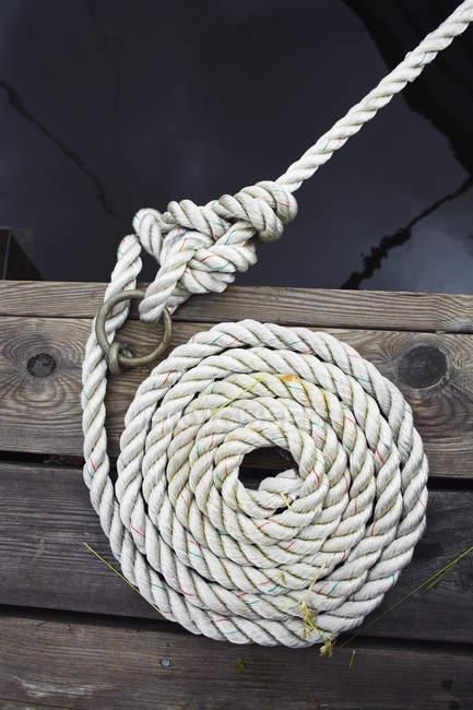 Згорнувшись причальні мотузку на дерев'яні поверхні — стокове фото