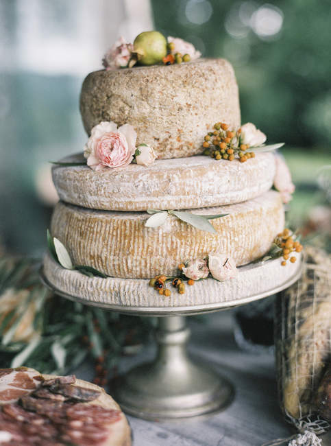 Italian cheese heads on cake stand decorated with flowers — стокове фото