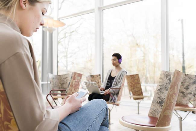 Femmes utilisant le smartphone et l'ordinateur portable assis dans la bibliothèque — Photo de stock