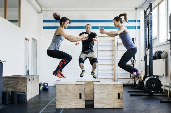 Young women and man jumping at gym — Stock Photo
