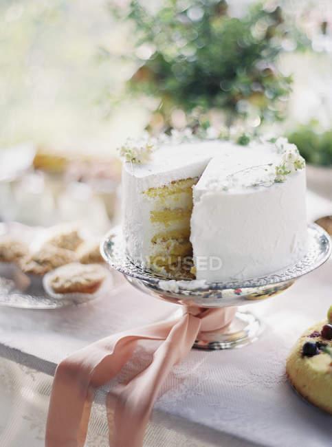 Pastel blanco en soporte de la torta con cinta rosa - foto de stock