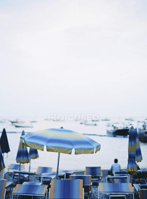 Beach umbrellas and deck chairs with sea on background — стокове фото