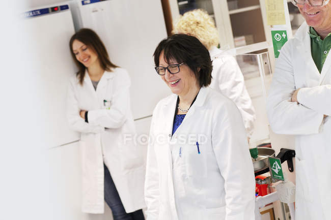 Scientists in lab coats standing smiling in laboratory — Stock Photo