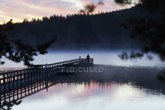 Vista lago e silhouette di persona sul molo al tramonto — Foto stock