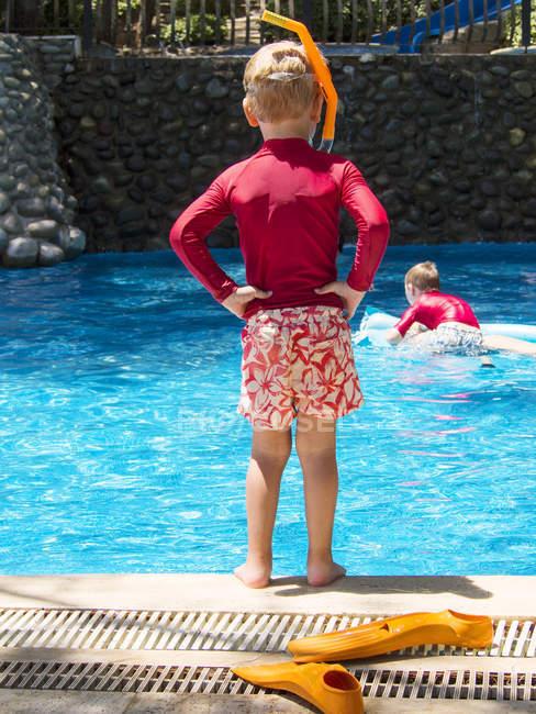 Rapaz usando boias flutuando na piscina — Fotografia de Stock