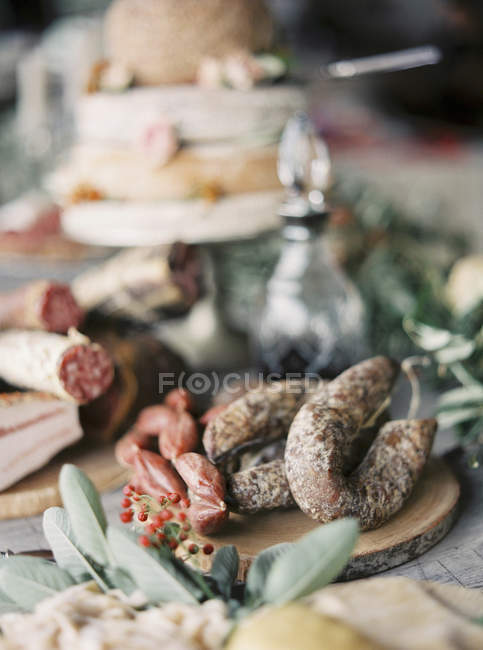 Cutting board with cured meats on table — Stock Photo