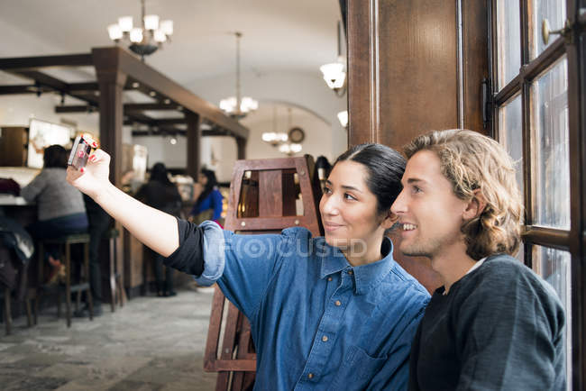 Young people taking selfie in cafe — Stock Photo