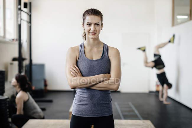 Портрет молодої жінки, стоячи в тренажерному залі з обіймами перетнула — стокове фото