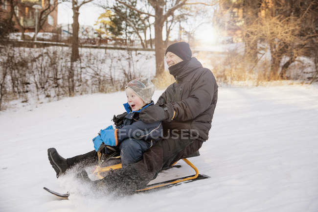 Father with son tobogganing, focus on foreground — Stock Photo