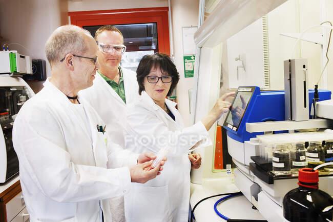 Hommes et femmes scientifiques en blouse blanche travaillant en laboratoire — Photo de stock
