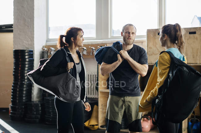 Young women and man with gym bags talking at gym, focus on foreground — Stock Photo