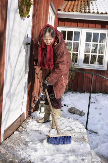 Senior woman sweeping snow, selective focus — Stock Photo