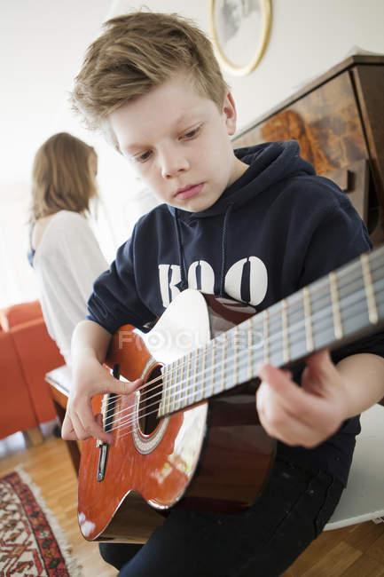 Garçon jouer de la guitare près de fille à la maison — Photo de stock