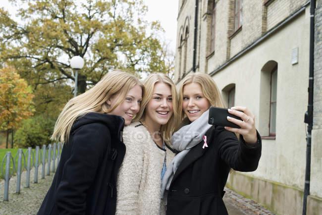 Mujeres jóvenes atractivas haciendo selfie en campus de la Universidad - foto de stock