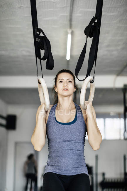 Young woman training on gymnastic rings — Stock Photo