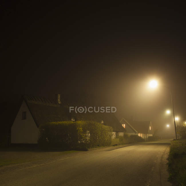 Foggy street and road illuminated at night — Stock Photo