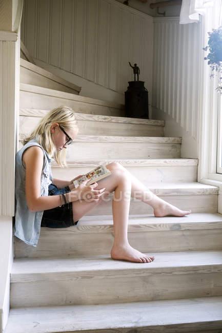 Jeune fille lisant livre sur des marches en bois à la maison — Photo de stock