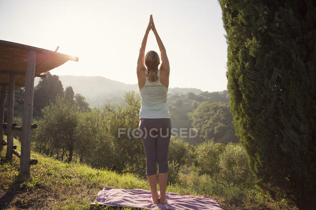 Woman practicing yoga against green hills — Stock Photo