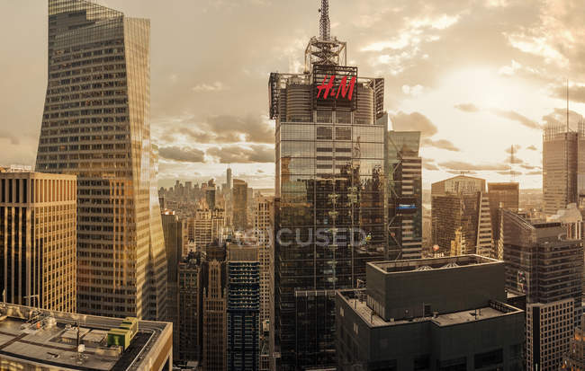 Cityscape with commercial sign at dusk, dramatic light — Stock Photo