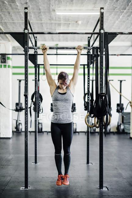 Giovane donna di formazione sulla barra orizzontale in palestra — Foto stock