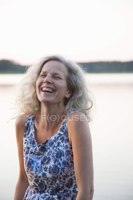 Портрет смеющейся женщины, озеро на заднем плане — стоковое фото