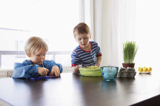 Girl and boy making Easter eggs, focus on foreground — Stock Photo
