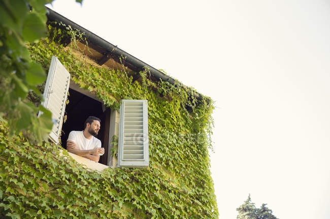 Man looking out from window of overgrown house — Stock Photo