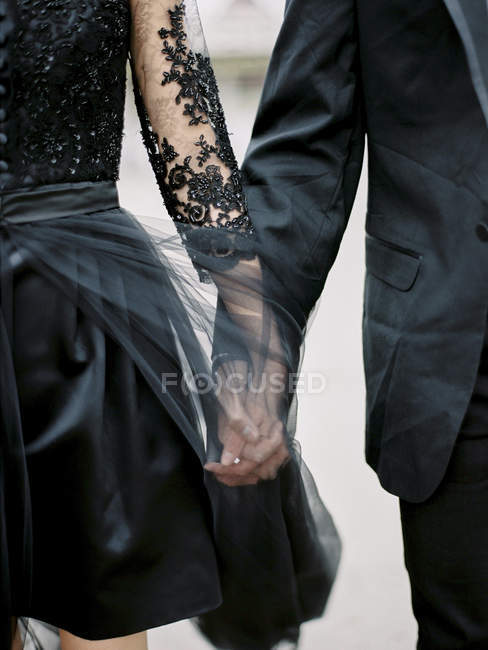 Young formally dressed couple holding hands, cropped shot — стоковое фото
